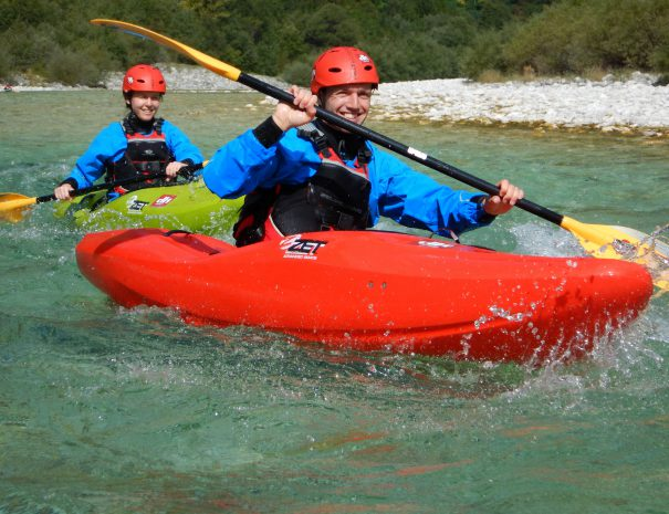 two beginners paddling rapids in a kayak slovenia