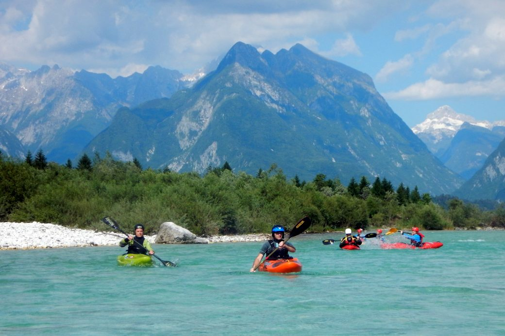 Group of kayakers paddling from Čezsoča with the mount svinjak in the back