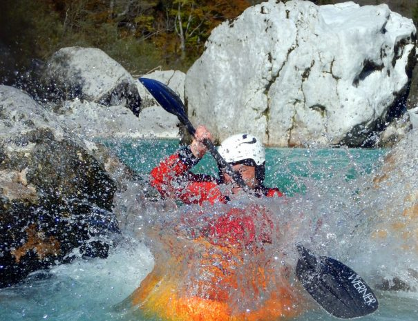kayaker jumping from rapids on kayak school in bovec