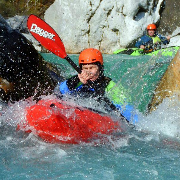 female paddling on emerald soča river