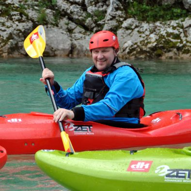 father having fun on easy kayak course with his family on soca river