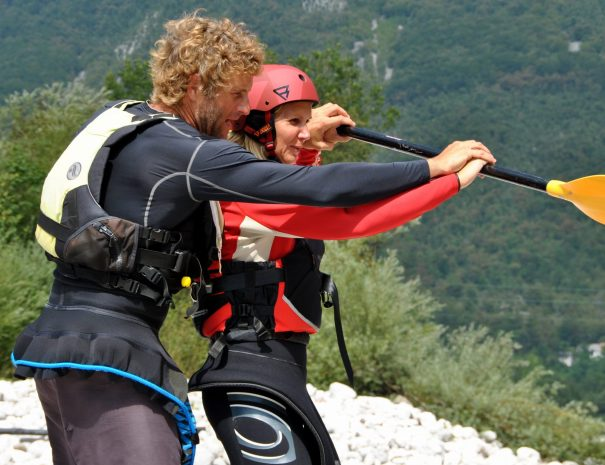 kayak instructor teaching mum how to hold paddle near river soča